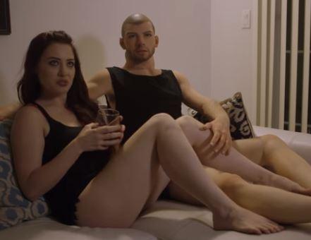 Hier sehen Sie die POrnodarstellerin Jessica Ryan mit einer männlichen Sexpuppe im Bett sitzen.